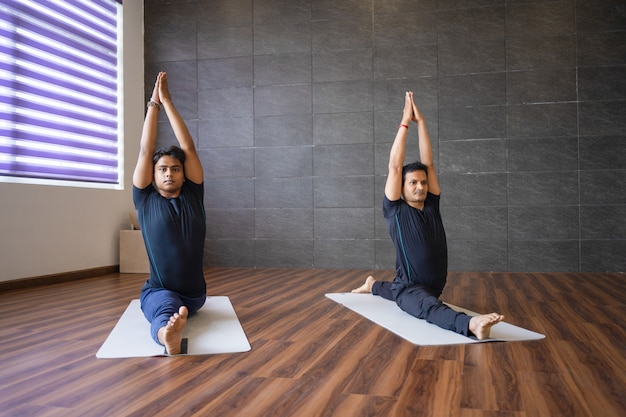 Two yogis doing monkey god pose in gym
