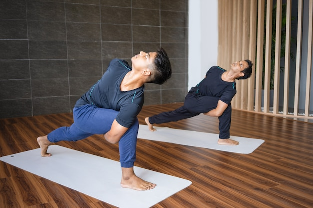 Two yogis doing revolved side angle pose in gym