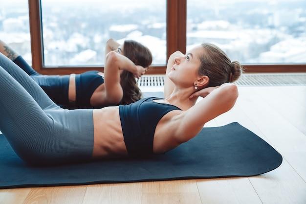 Две молодые активные женщины с тонким телом делают пресс, лежа на циновках на полу, тренируют концептуальную подготовку, тренируя фитнес-аэробику.