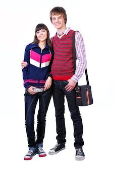 Двое молодых взрослых студентов, мальчик и девочка, стоя на белом