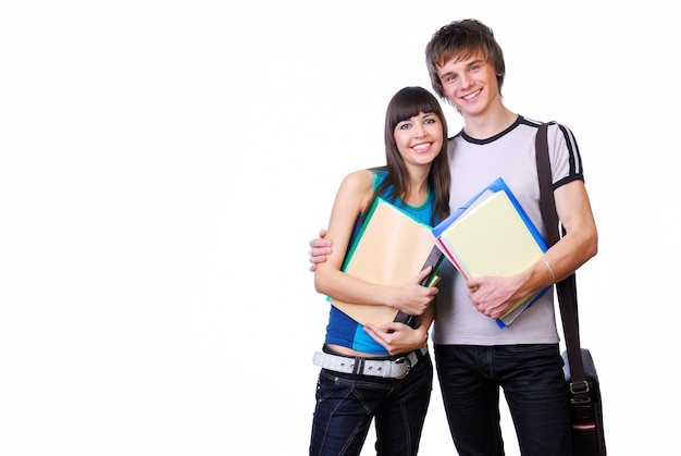 Two young adult students standing and embracing isolated on white
