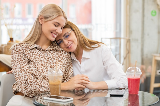 Две молодые ласковые девушки-шопоголики в элегантной повседневной одежде сидят за столиком в кафе, пьют и наслаждаются отдыхом после покупок