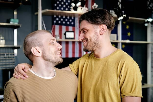 두 젊은 다정한 게이 남자 껴안고 서로 보고