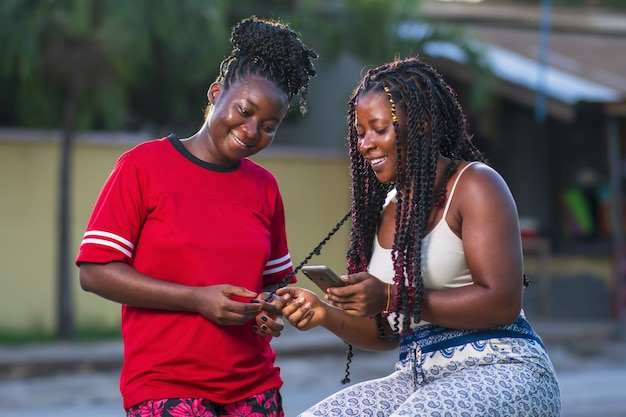 Two young african american female friends looking at a phone and smiling