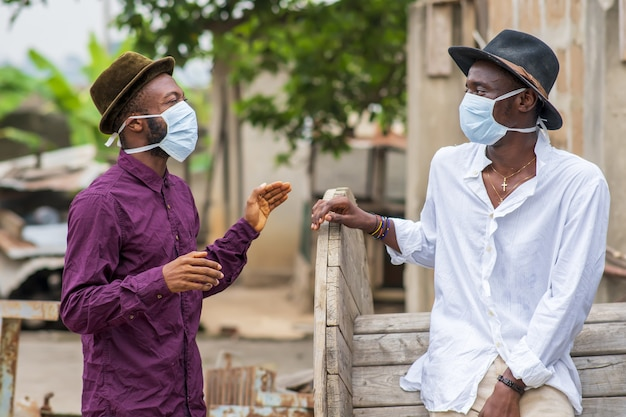 Two young african american male friends in protective face masks laughing and social distancing