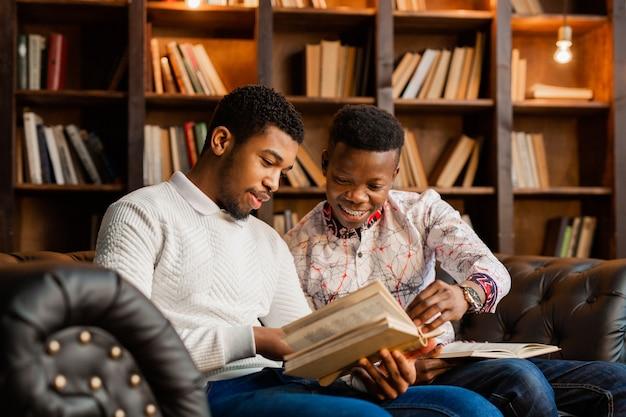 2人の若いアフリカ人男性が本と一緒にソファに座っています