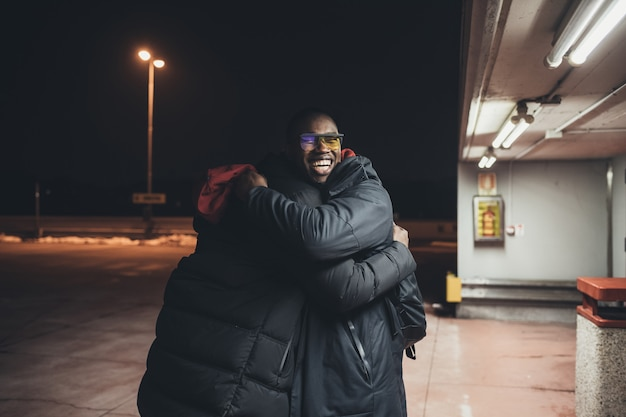 Two young african men outdoor together hugging having fun