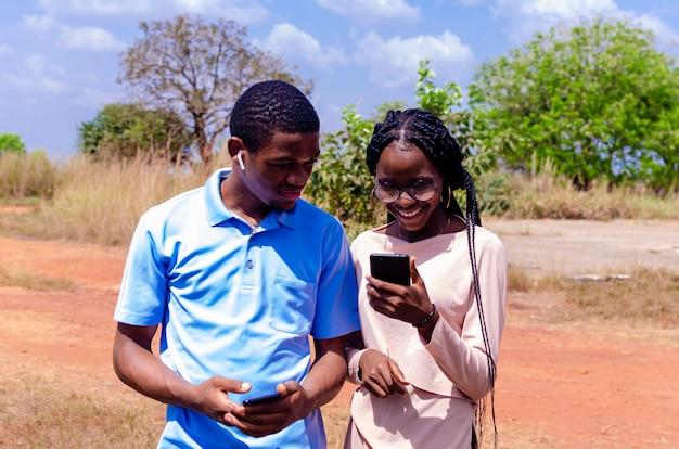 彼らが彼らの携帯電話で見たものに興奮していると感じている2人の若いアフリカの学生