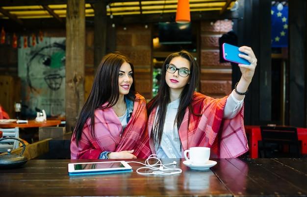 두 명의 젊고 아름다운 소녀가 테이블에 앉아 카페에서 셀카를 찍고 있다