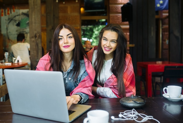 두 명의 젊고 아름다운 소녀가 테이블에 앉아 인터넷에서 무언가를 찾고 있습니다