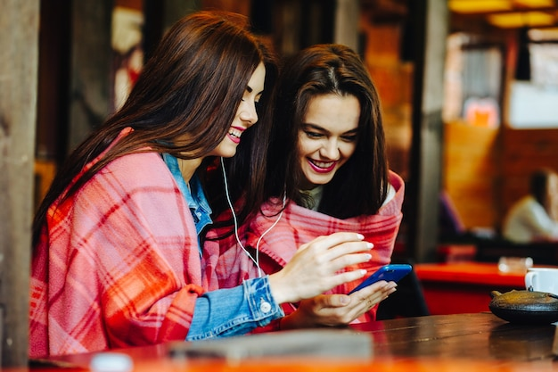 スマートフォンで音楽を聴いてテーブルに座っている2人の若くて美しい少女