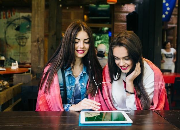 테이블에 앉아 태블릿으로 무언가를 보고 있는 두 명의 젊고 아름다운 소녀