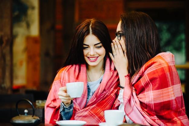 一杯のコーヒーとテラスでおしゃべりする2人の若くて美しい女の子