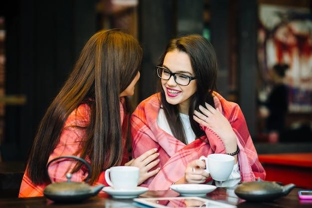 두 젊고 아름다운 소녀들이 커피 한 잔과 함께 테라스에서 수다를 떨고 있다