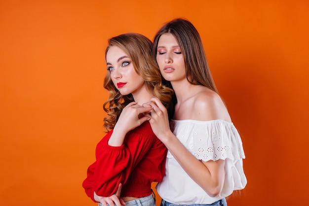 2人の若くて美しい女の子は、オレンジ色の背景のスタジオで感情と笑顔を示しています。広告のための女の子。