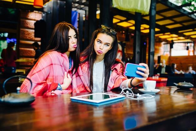 テーブルに座ってカフェで自分撮りをしている2人の若くて美しい女の子