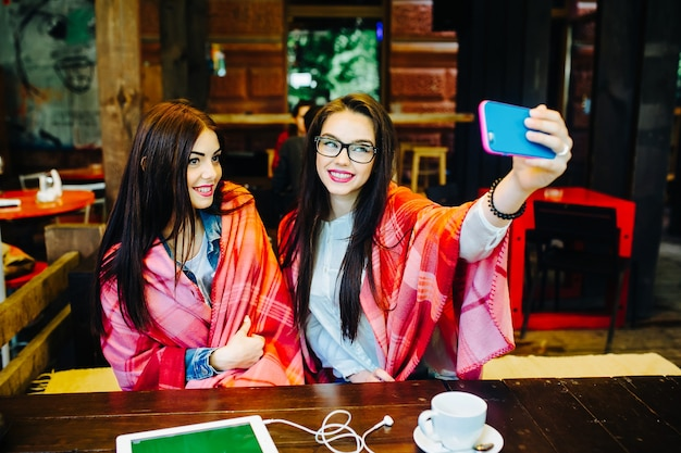 Две молодые и красивые девушки сидят за столом и делают селфи в кафе