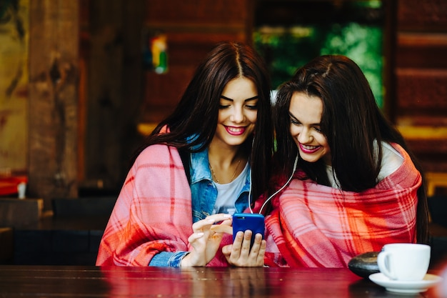 スマートフォンで音楽を聴いてテーブルに座っている2人の若くて美しい女の子