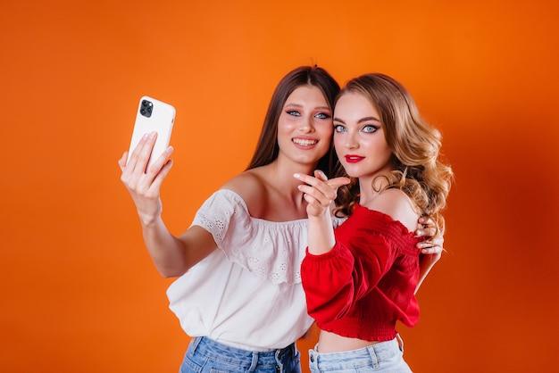 2人の若くて美しい女の子が自分撮りをして、紫色の背景のスタジオで携帯電話を見ています。広告のための女の子。