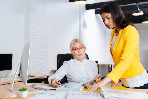 Две молодые и зрелые бизнес-леди после встречи в офисе