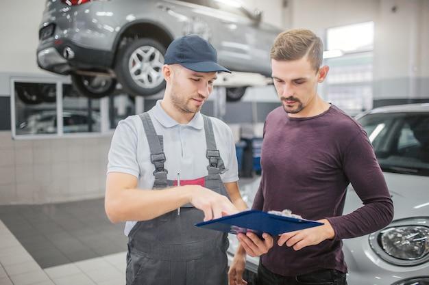 2人の若くて深刻な男性がガレージに立っています。彼らは、書類が入ったプラスチック製のタブレットを持っています。それらの均一なポイントの男。