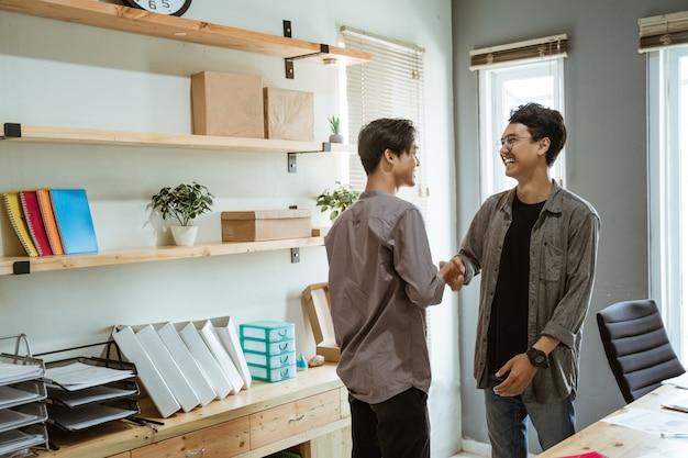 Два молодых азиатских деловых человека пожали друг другу руки в согласии