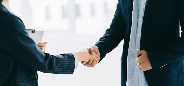 契約を締結した後、2人の若いアジア人ビジネスマンが握手
