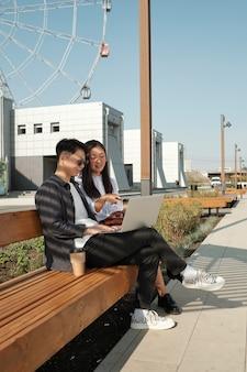 야외에서 프레젠테이션을 준비하는 두 젊은 아시아 직원