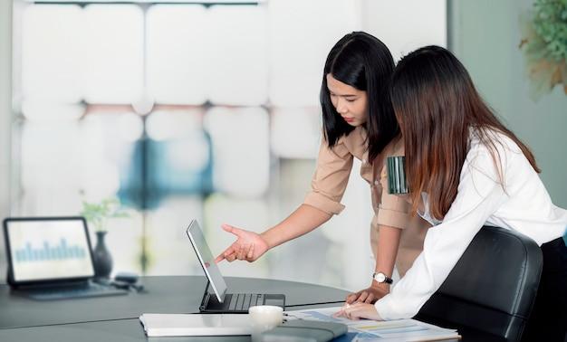 Две молодые азиатские женщины обсуждают бизнес-план в офисе.