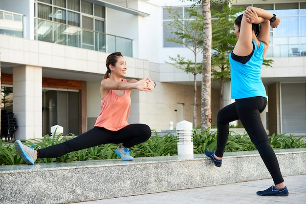 Two young asian female joggers stretching in city street