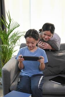 Две молодые азиатские девушки вместе играют в видеоигры дома.