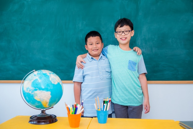Two young asian student standing and smiling in front of chalkboard at school