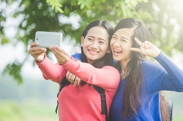 Two young asian students taking selfie