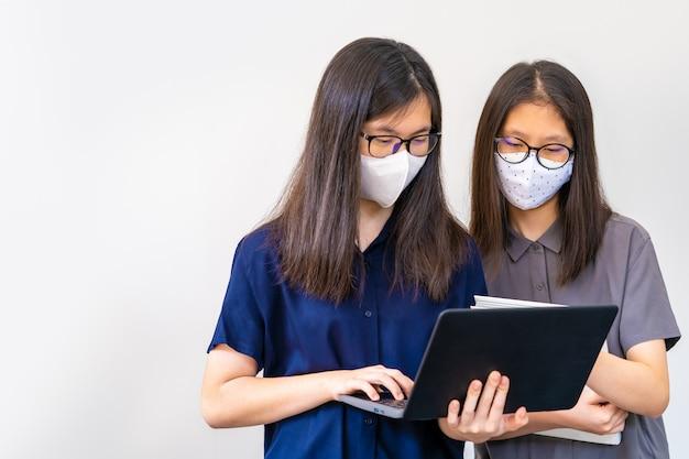2人の若いアジアのティーンエイジャー、マスクを着用し、学校のプロジェクトで近づきすぎ