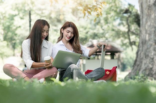 두 명의 젊은 아시아 대학생이 공원의 큰 나무 아래 푸른 잔디에 앉아 컴퓨터를 사용하고 행복과 함께 이야기를 나누었습니다.