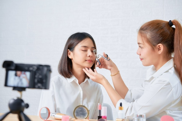 Two young asian woman beauty vlogger video online is showing make up on cosmetics products and live video on digital digital camera.