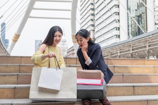 2 人のアジアの若い女性が興奮して買い物袋を持ち、都会の階段を見ている