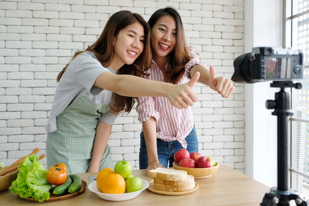 Two young asian woman food bloggers talking while recording video