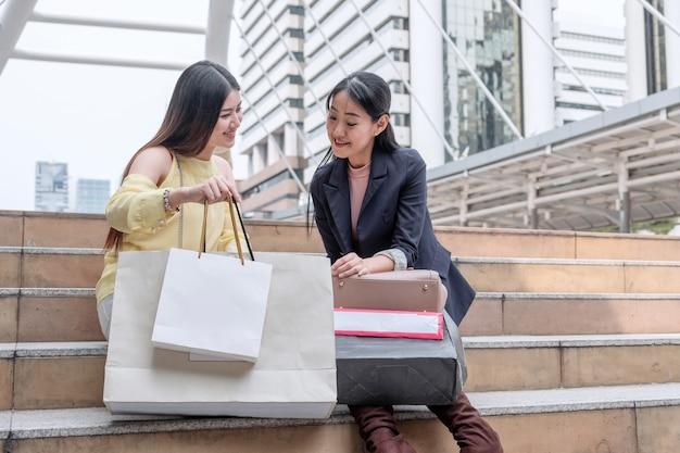 買い物袋を持ち、都市の階段を見ている 2 人の若いアジア女性