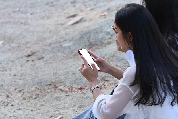 Две молодые азиатские женщины сидя на внешнем и используя мобильный телефон.