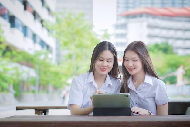 2人の若いアジアの女性学生が一緒に相談し、タブレットを使用して情報を検索しています