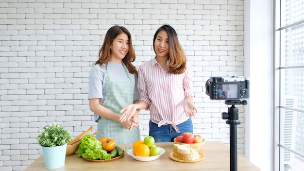 Two young asian women food bloggers talking while recording video with happy moment