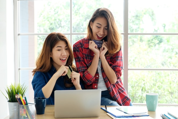 Two young asian women holding credit card and using laptop computer for shopping online