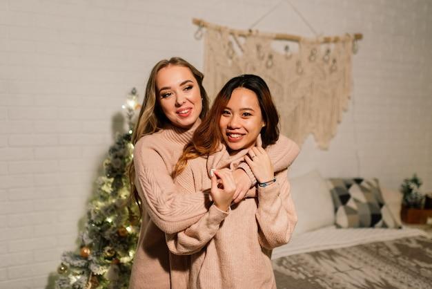 Две молодые азиатские женщины, улыбаясь от счастья на рождественской вечеринке, лгбт-паре, праздновании друзей