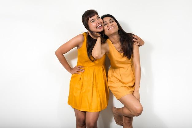 Две молодые азиатские женщины вместе против белого пространства