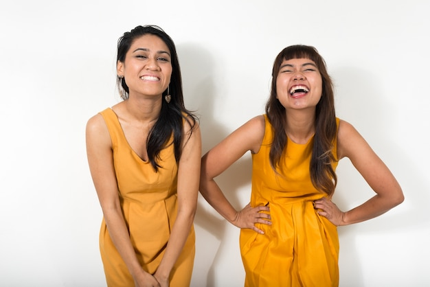Two young asian women together against white space