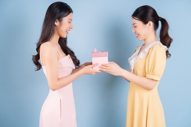 파란색 배경에 드레스를 입고 두 젊은 아시아 여성