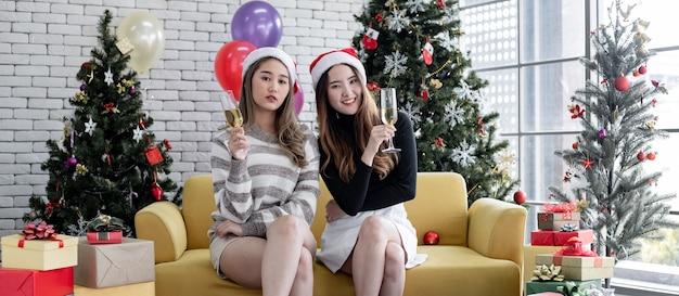 Две молодые азиатские женщины с бокалами и пили вино дома, чтобы вместе отпраздновать рождество