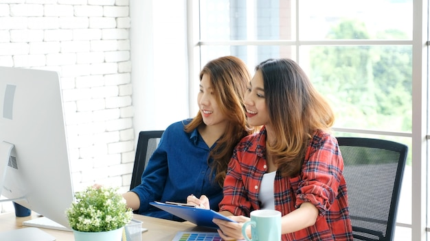 Two young asian women working with computer at home office with happy emotion, working at home, small business, office casual lifestyle concept