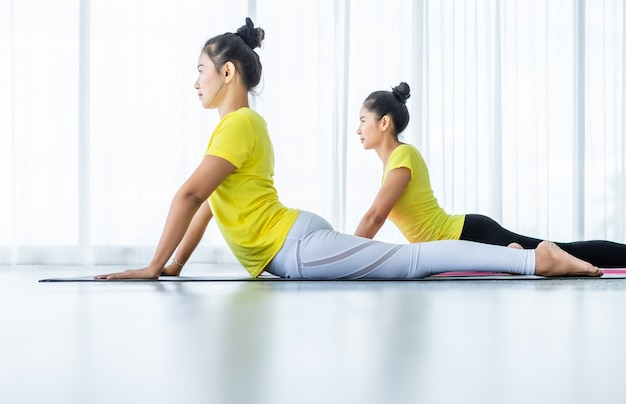 Two young asian women workout practicing yoga in yellow dress or pose with a trainer and practice meditation wellness lifestyle and health fitness concept